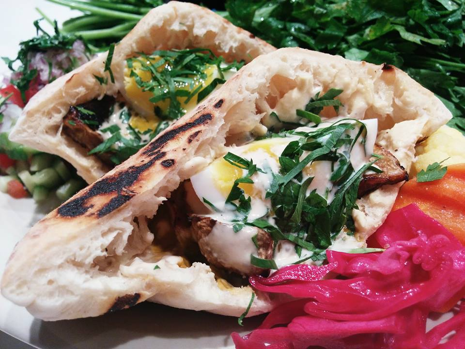 The stuffed pita is a massive sandwich that comes with a side of Israeli salad.