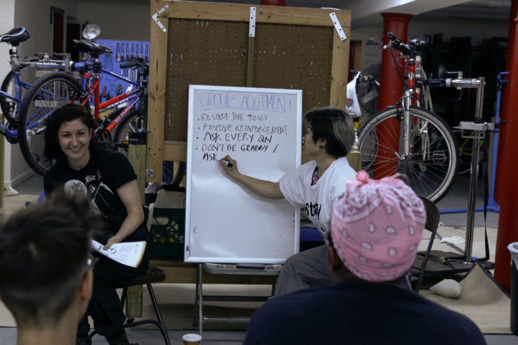 Instructor Sera Stavroula and organizer Denise Mei take note of the class rules at class 3 of the W/T/F Bicycle Repair and Maintenance Intensive on March 29 at the Lutheran Church of St John the Evangelist in Brooklyn for women/trans/non-binary identifying individuals.