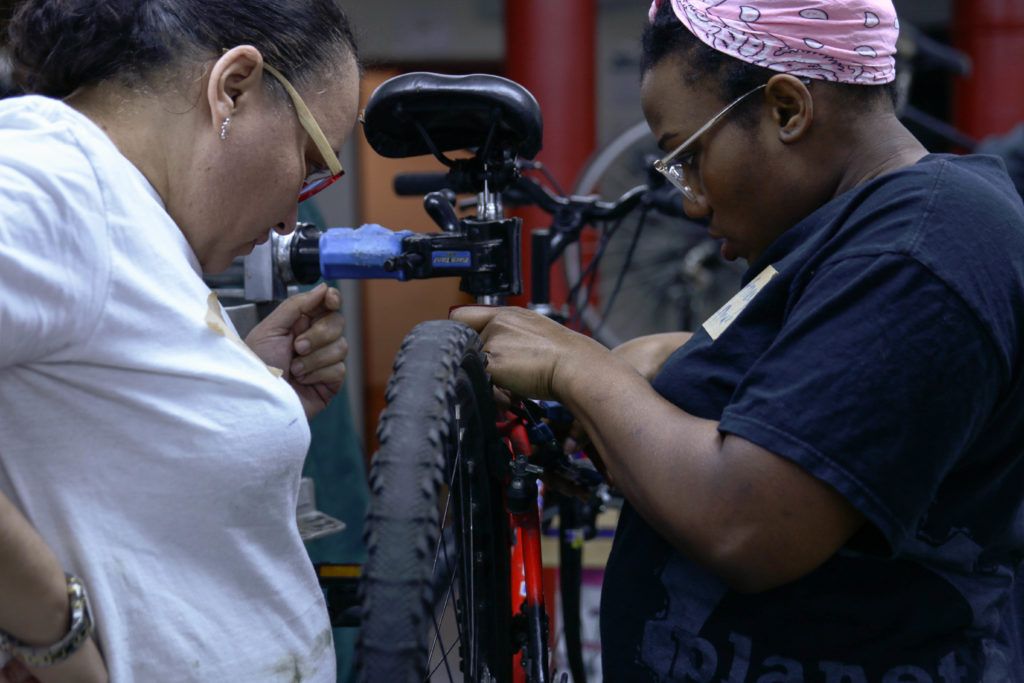 Madeline Abreu and Courtney Williams team up on a set of brakes at class 3 of the W/T/F Bicycle Repair and Maintenance Intensive on March 29 at the Lutheran Church of St John the Evangelist in Brooklyn for women/trans/non-binary identifying individuals.