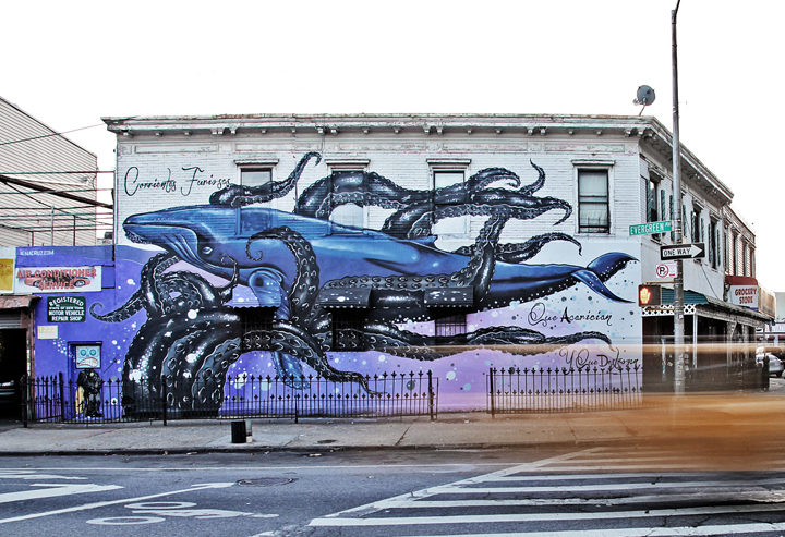 A mural of a blue whale being entangled in the tentacles of a giant squid takes up the side of a building on Evergreen and Myrtle in Bushwick. Photo: Stefano Ortega