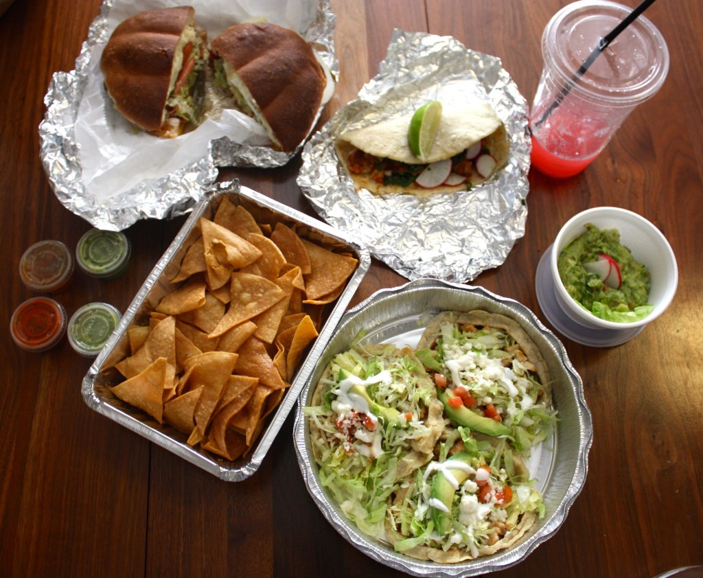 A takeout smorgasboard from Taqueria Milear: Sopes, fresh chips, chorizo torta, taco with homemade torillas, watermelon juice, and guacamole.